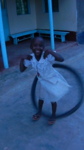 "Joy with a bike tire ""hulahoop"".  No...her name is Joy."