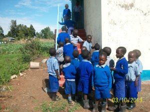 Kids lined up to check out the new latrine.  There are 3 more doors on the other side.