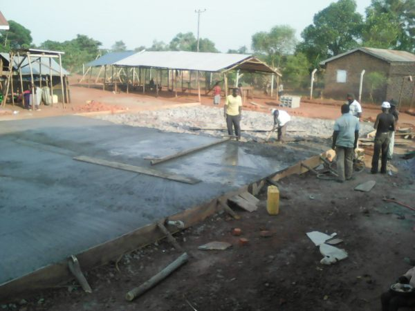 Concrete poured over the foundation, one wheel barrow load at a time.